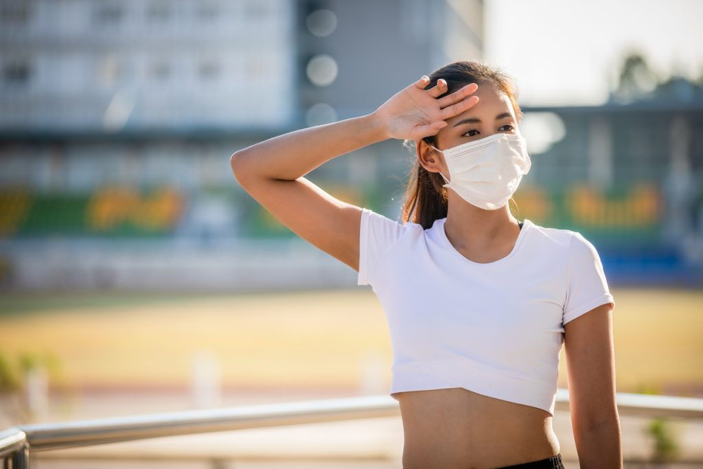 Asian Young fitness sport woman is resting tired and she wears a mask for protective Dust and pollution on city