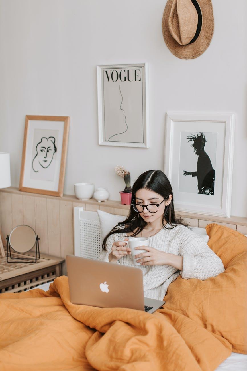 woman having coffee and using laptop in bed