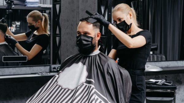 woman-barber-cutting-hair-bearded-man-face-mask-quarantine-haircut-concept_230325-416